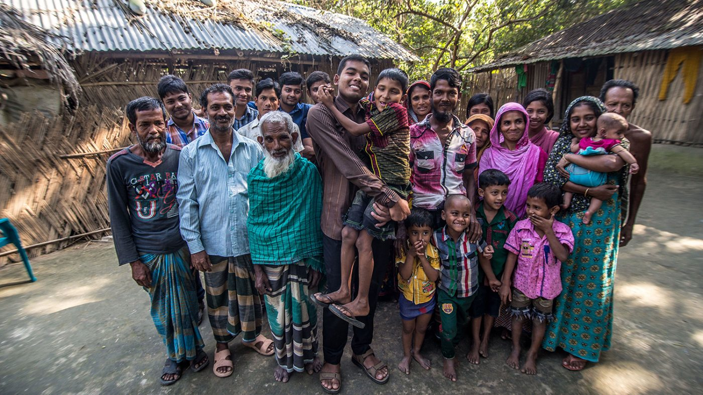 Polok Islam is being held by a family member. Around 20 other people are in the group photo, all are smiling and standing.