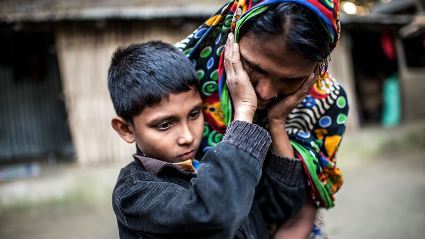 Cataract patient Polok Islam, 9, photographed with his mother, Hasna Khatun, at home in Salikupah village, Bangladesh. He is holding his hands up to his mother's face, feeling her cheeks. Both Polok and Hasna are looking down to the ground.