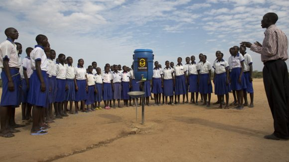 Children stand outside singing about facewashing in Kenya. There are around 20 of them, all wearing blue skirts and white polo tops.
