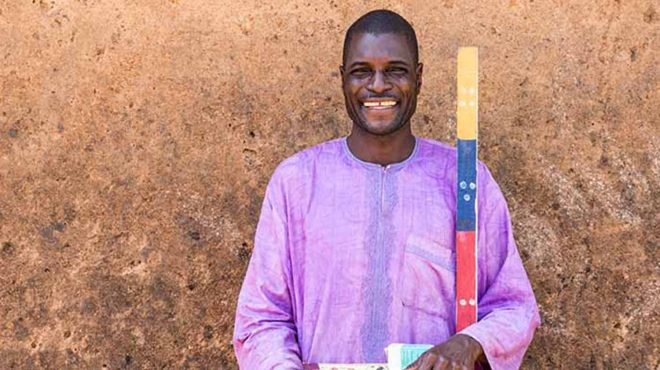 Ayuba Auta, Mectizan distributor in Bugai, stands against a wall with a dosing pole. He is wearing purple and smiling.