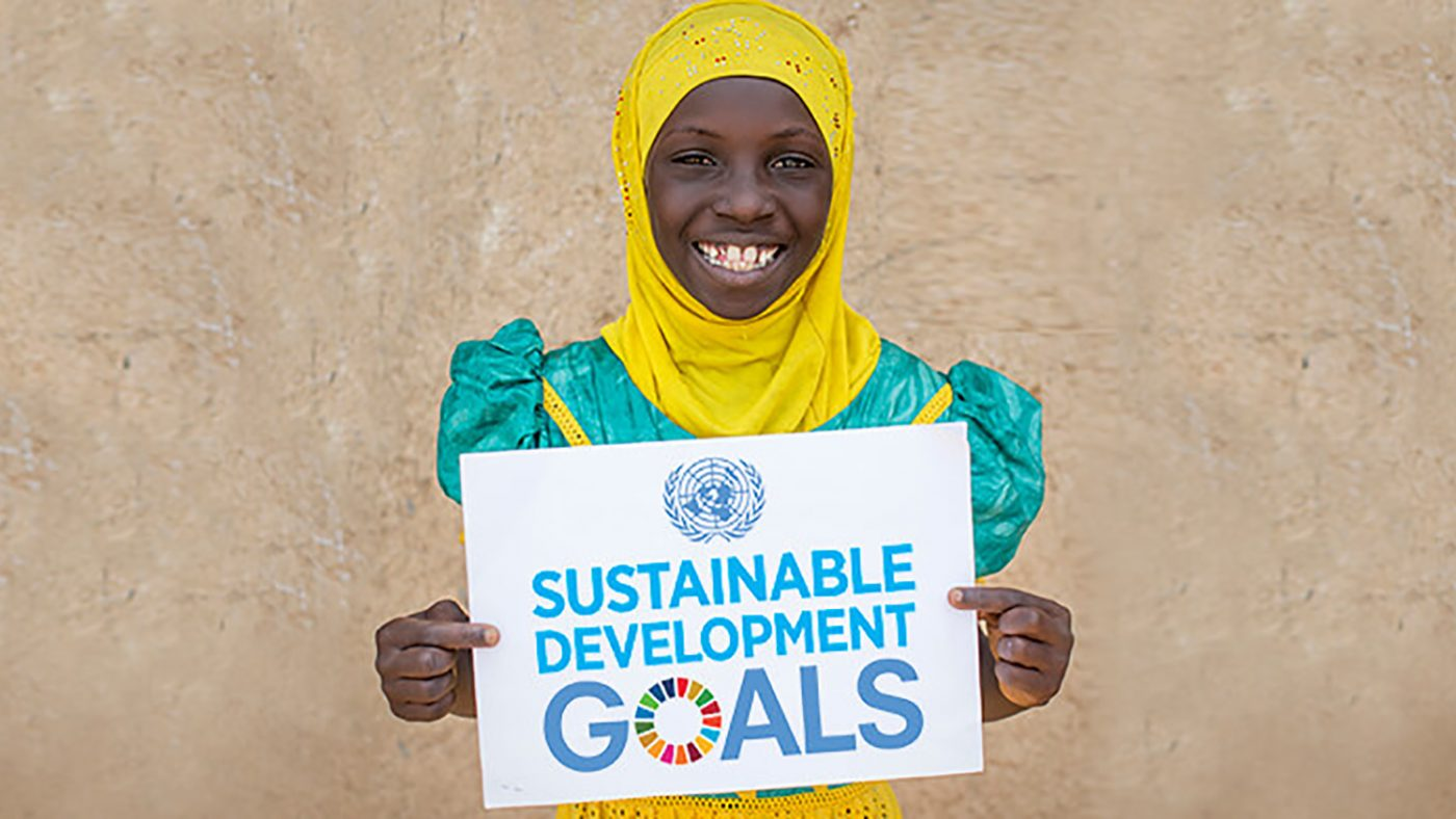 A girl holds a sign saying 'Sustainable Development Goals'.