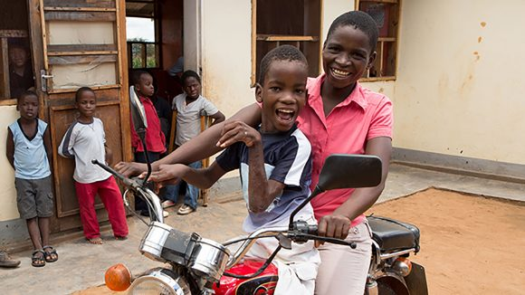 Two boys in Malawi smile and laugh as they ride a motorbike in front of a group of their friends.