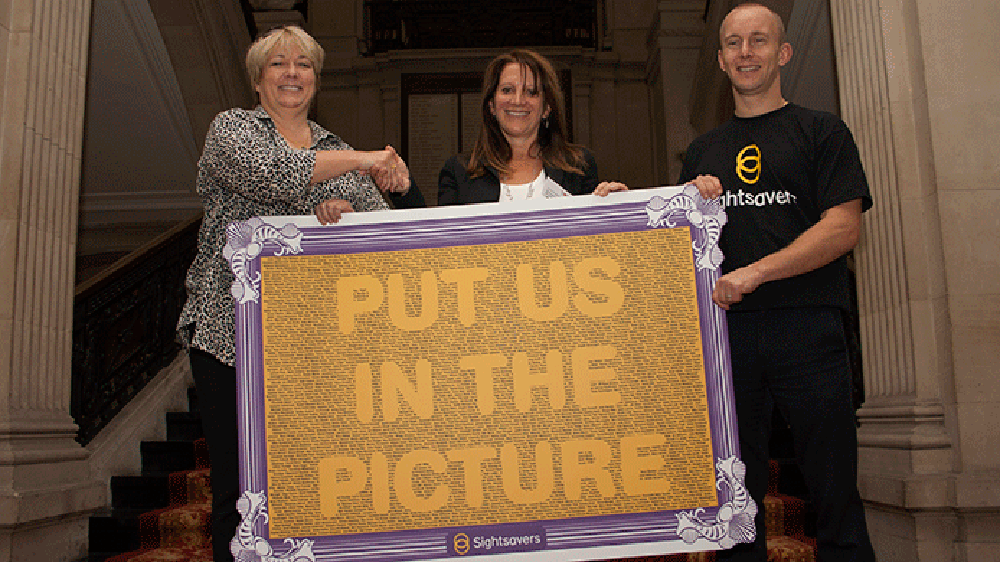 Caroline Harper, Lynne Featherstone and Ben Quilter holding a giant card reading 'Put Us in the Picture'.