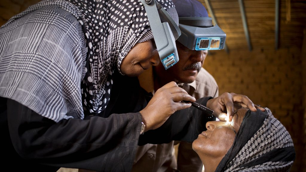 An eye health worker examines a woman's eyes for signs of trachoma.