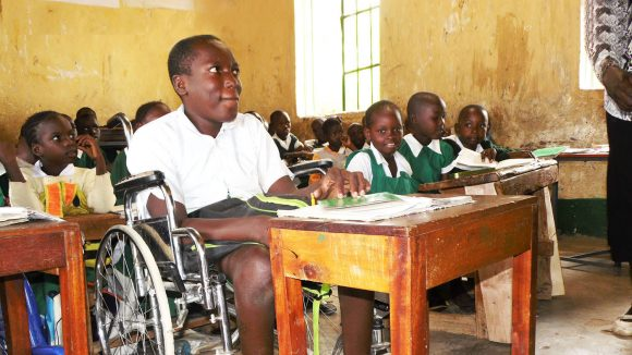 Flash sits at his desk in a wheelchair in school, surrounded by his classmates as they listen to their teacher.