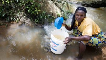 A woman crouches in a stream using a bucket to collect water in Nigeria.