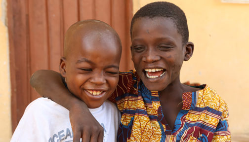 Two boys smile and embrace each other.