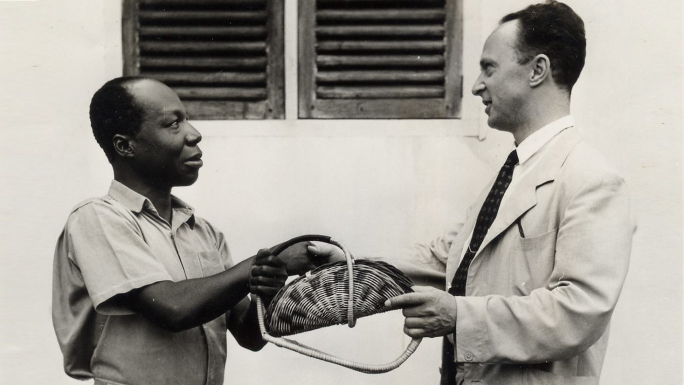 Sir John Wilson meets a local man and is presented with a gift during a visit to Ghana.
