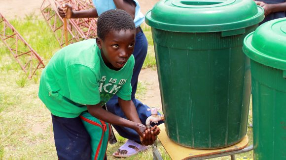 A schoolboy from Mwase villagein Zambia washes his hands with water from a large green tank.