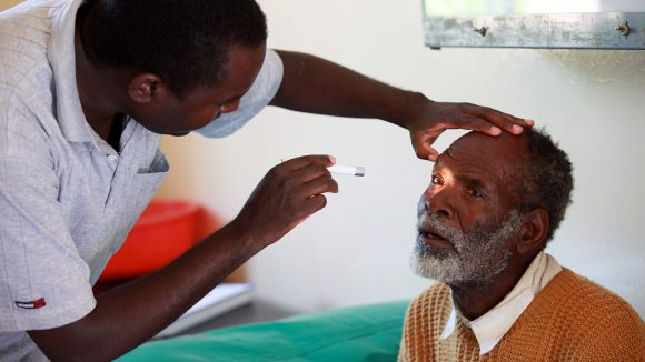 An older man in Zambia has his eyes examined by a doctor, who holds one of his eyes open and shines a light into it.