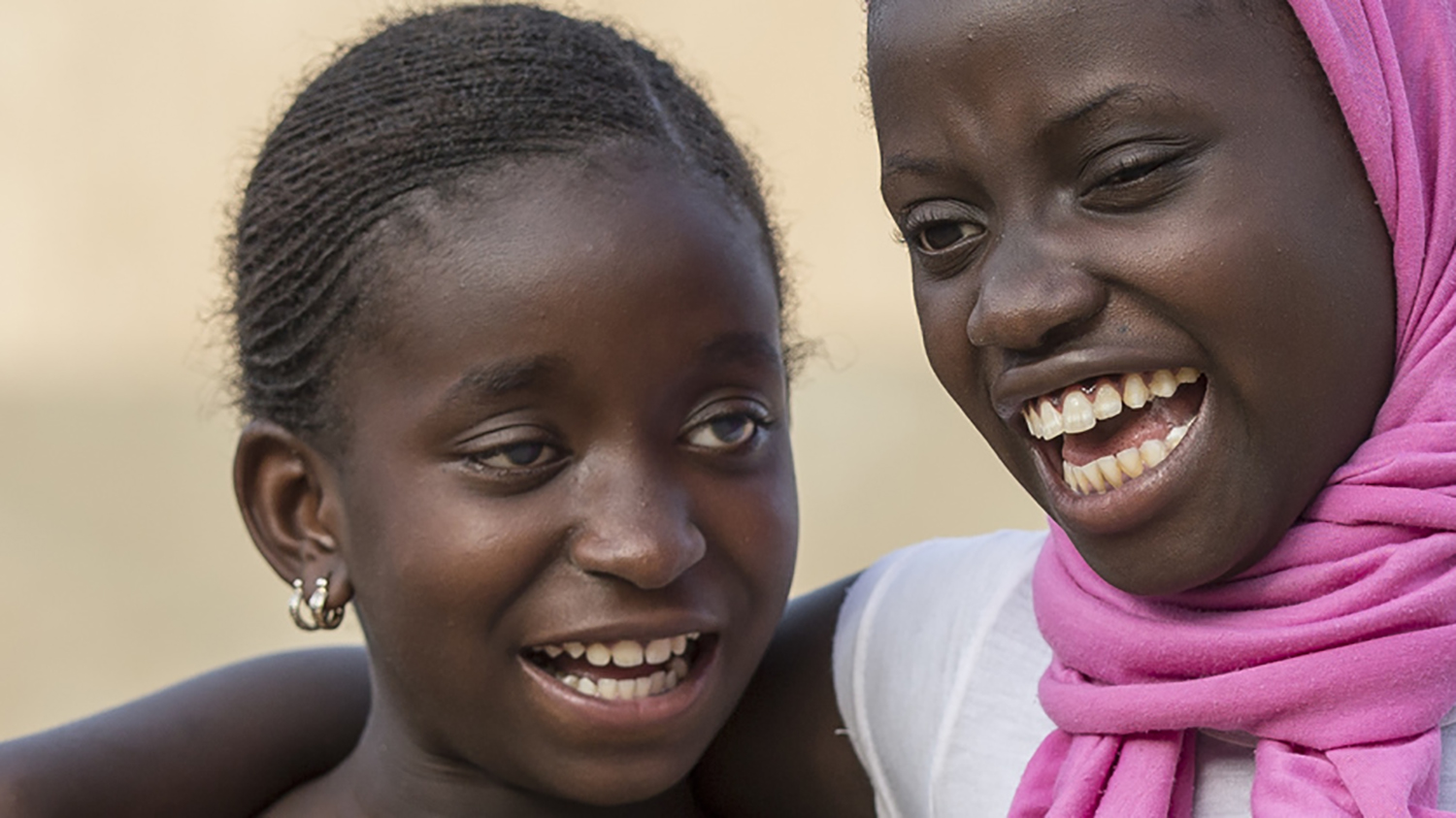 Two girls with visual impairments smile as they embrace each other.