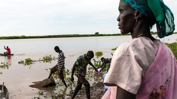 A woman with visual impairment stands beside a river as a group of men carry out their work gathering rubbish from the river.