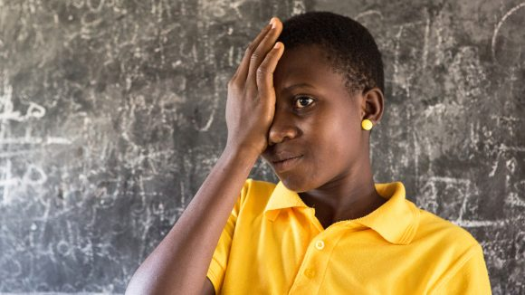 A girl covers her eye with one hand during a sight test at a school on Ghana.