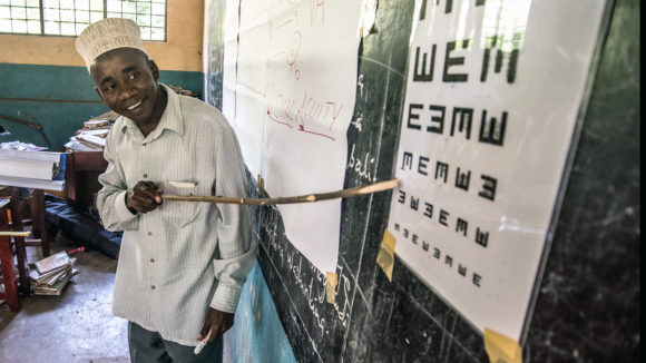 A teacher in Zanzibar uses a chart to test children's vision.