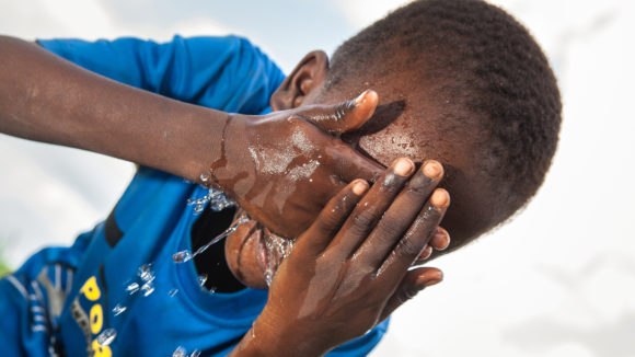 A boy washes his face to prevent the spread of trachoma infection.