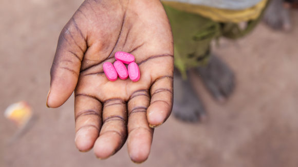 A child in Senegal holds antibiotic tablets in his hand.