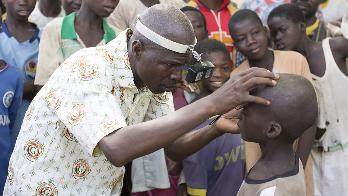 A health worker in Nigeria examines a boy's eyes to check for trachoma infection.