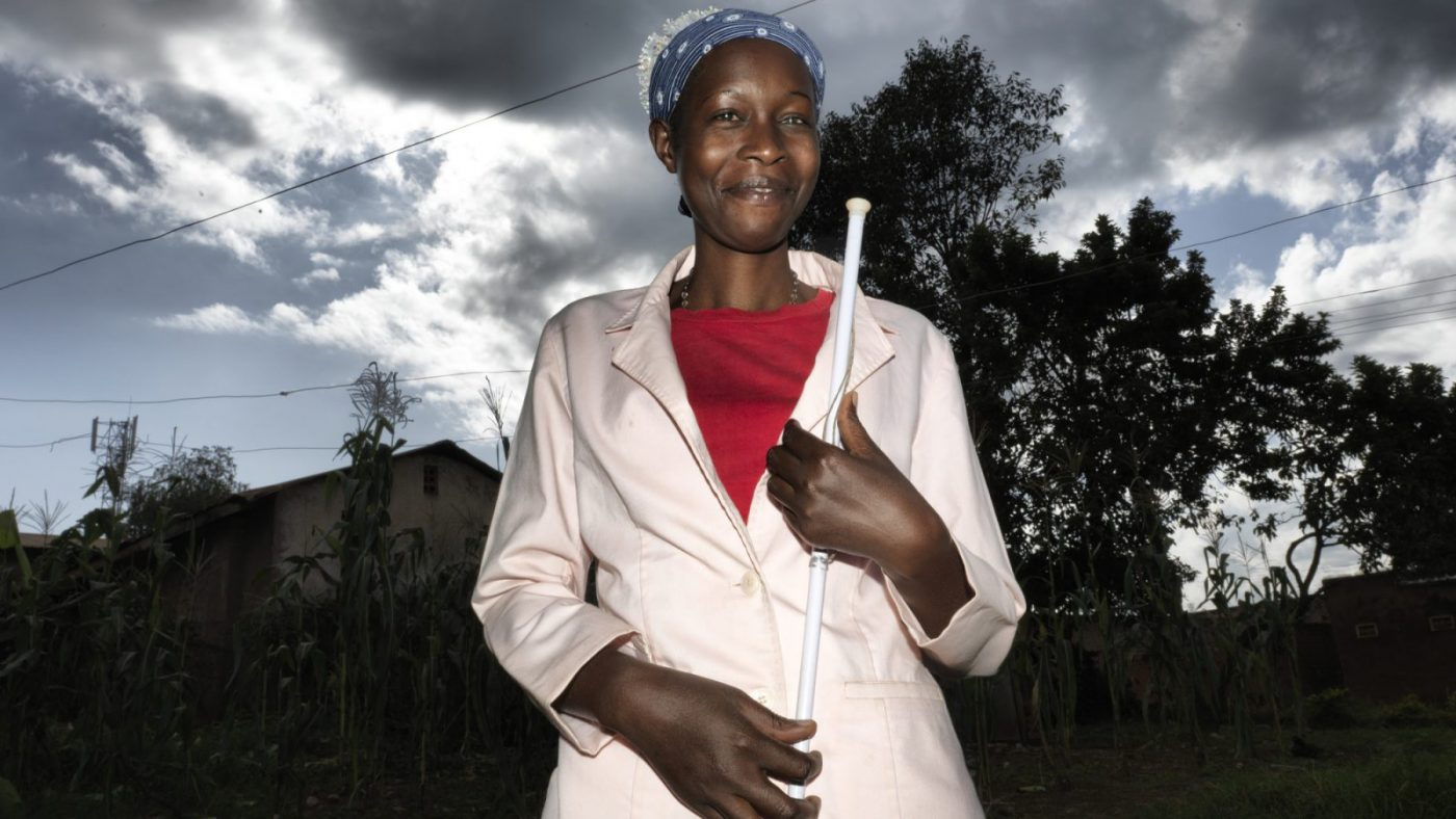 Woman holding white stick, smiling at camera.
