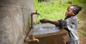 Girl washing hands in outside sink.