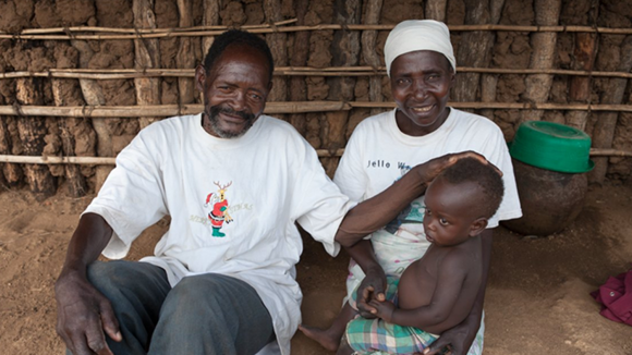 Winesi March sitting with his wife who has their grandson on her lap.