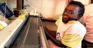 Emily, who has physical disabilities, smiles at the camera as she works on an embroidery machine.