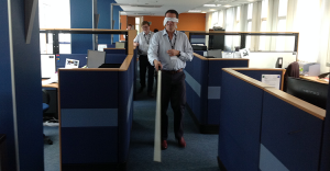 A man wearing a blindfold and holding a white cane, walking around an office.