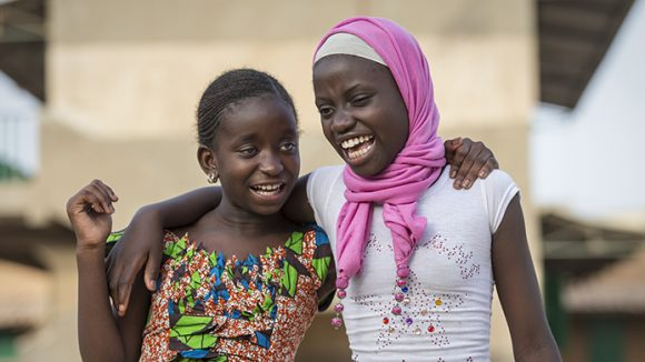 Two young girls named Fatou and Bineta smiling with their arms over each other's shoulders.