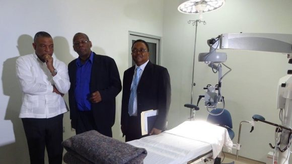 Three men standing next to an empty hospital bed in Jamaica.