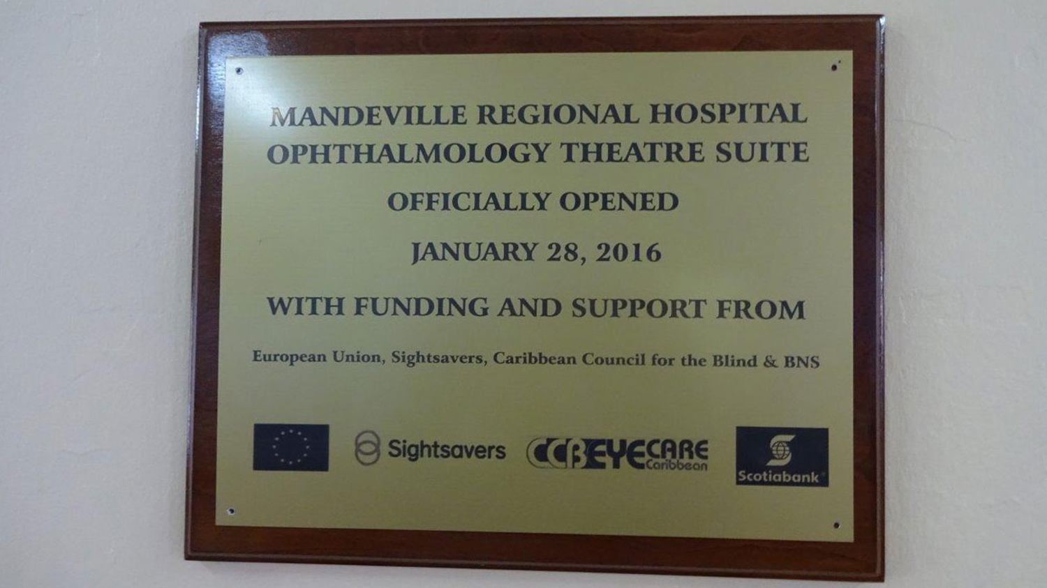 A photo of a plaque stating the Mandeville Regional Hospital Ophthalmology Theatre Suite officially opened in January 2016 with funding and support from the EU, Sightsavers, Caribbean Council for the Blind and BNS.