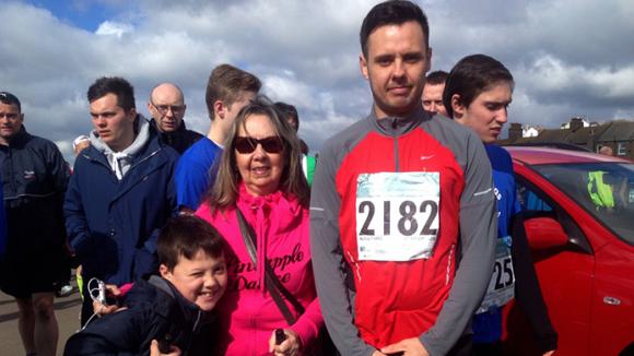 Marathon runner standing with family.