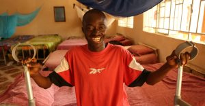 A young boy sitting on bed holding onto crutches smiling happily.