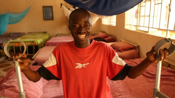 Young boy sitting on bed holding onto crutches smiling happily.