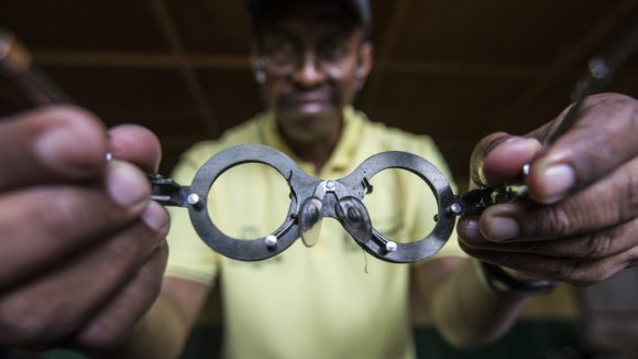 Man holds pair of glasses towards camera.
