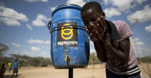 A boy washes his face next to a Sightsavers water tank.