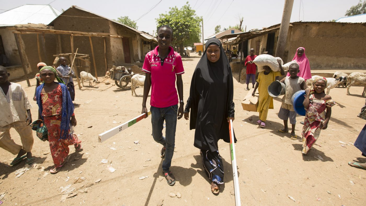 Two community volunteers in Yantodo, Nigeria, walk through their village with their dose poles to distribute treatment.