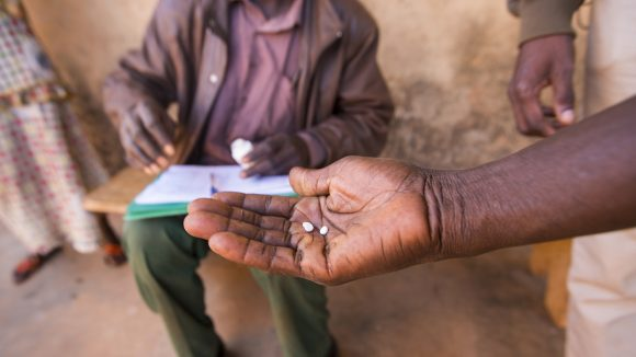 A hand holds medication used to treat NTDs.