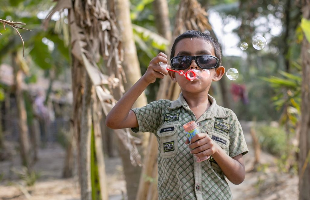 A young boy wearing dark glassed blowing bubbles.