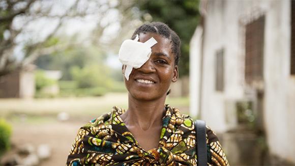 Lady with bandage over eye.