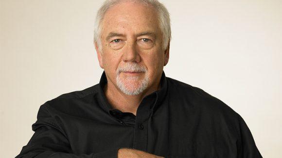 Portrait of Brien in black shirt against white background.