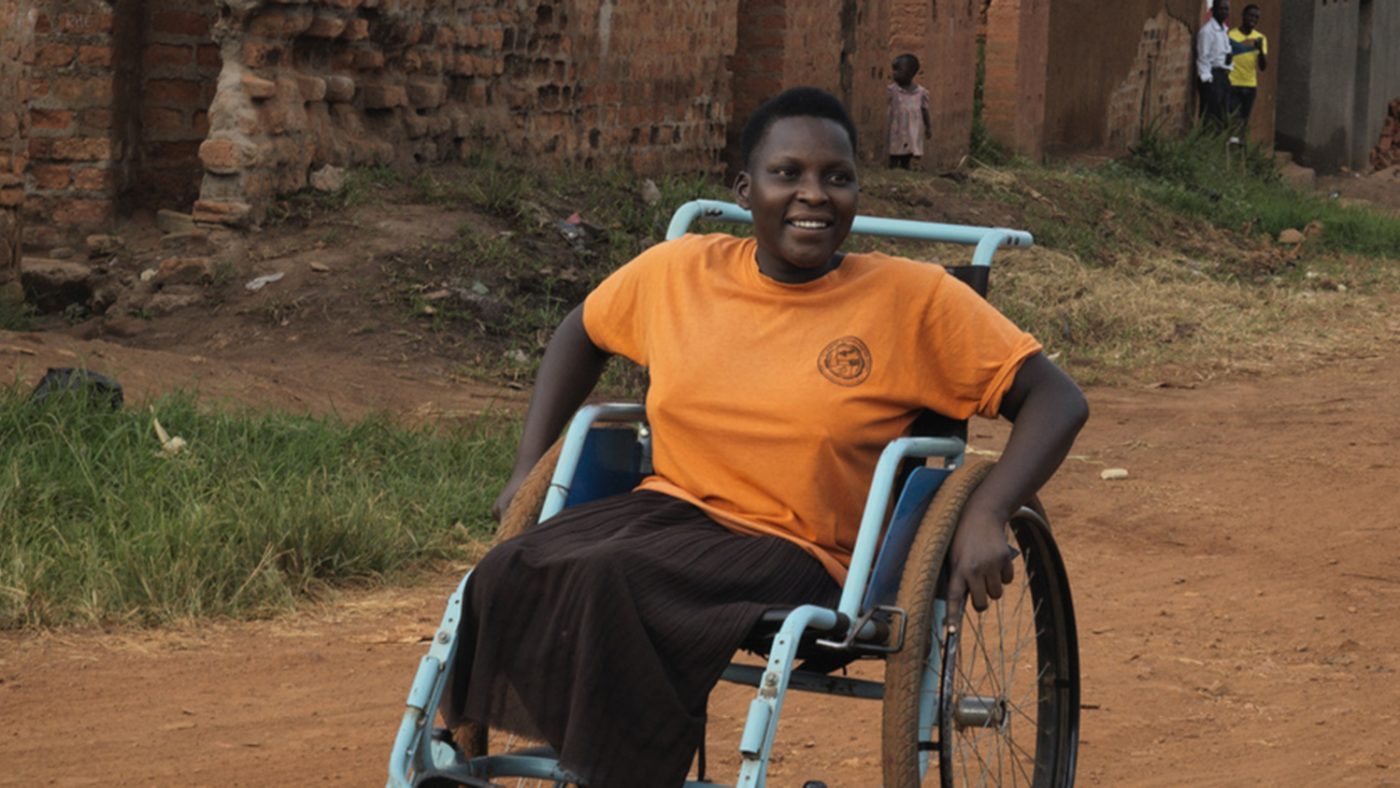 A young woman sitting in her wheelchair on a dirt road.