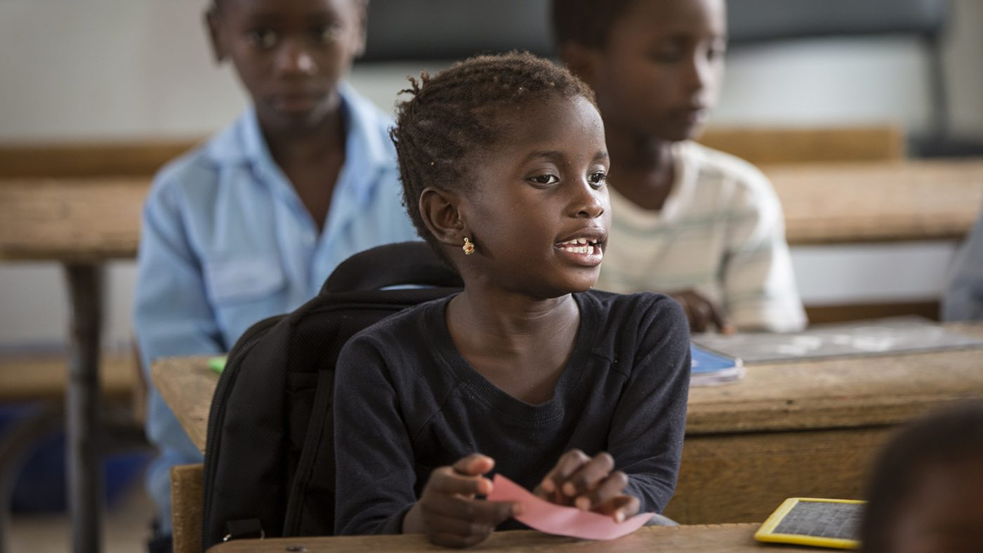 Aminata Gueye is wearing a dark top, sitting at a desk, talking.