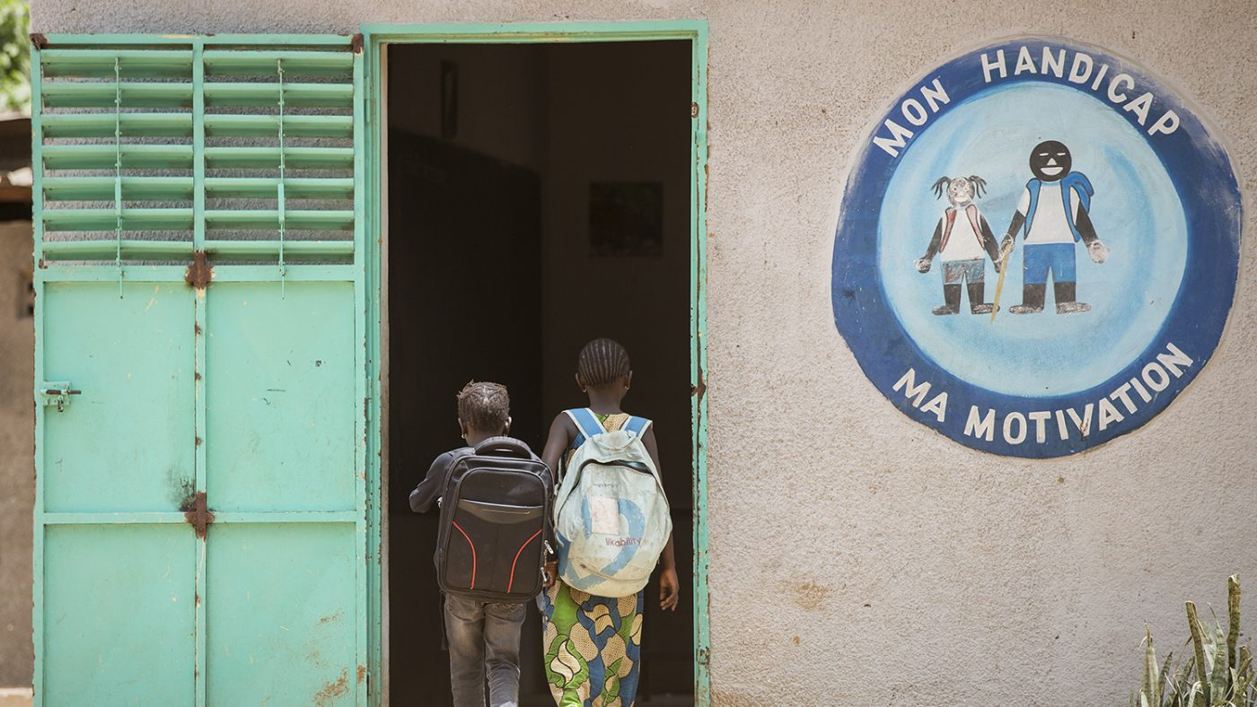 Two girls walking through a door in a school. The sign beside them reads Mon handicap, ma motivation.