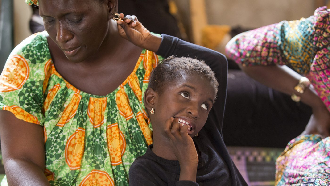 Aminata Gueye has one hand near her mouth and the other close to her mother. She is sitting on her mother's lap.