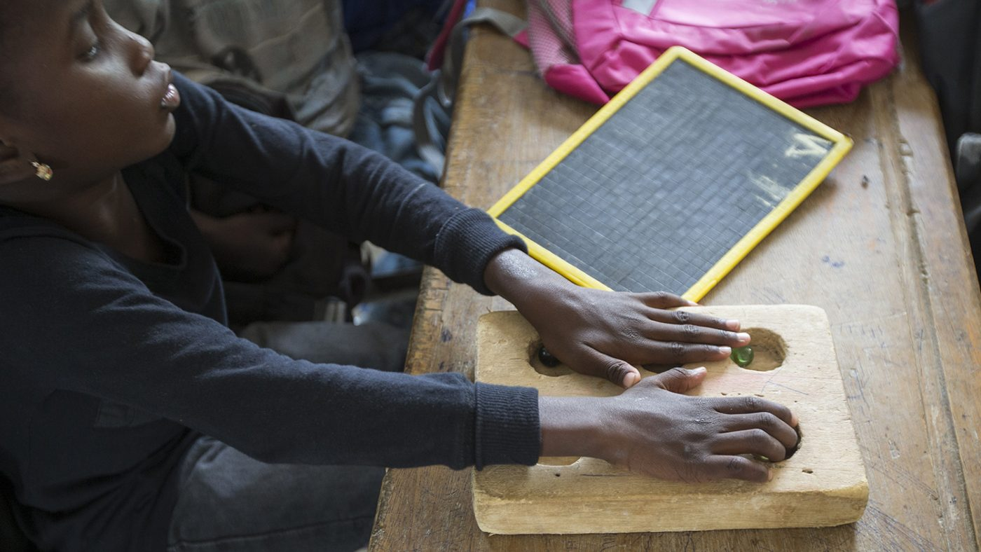 Aminata Gueye has her hands over a wooden block. Her eyes are closed and she is feeling the round holes in the block.