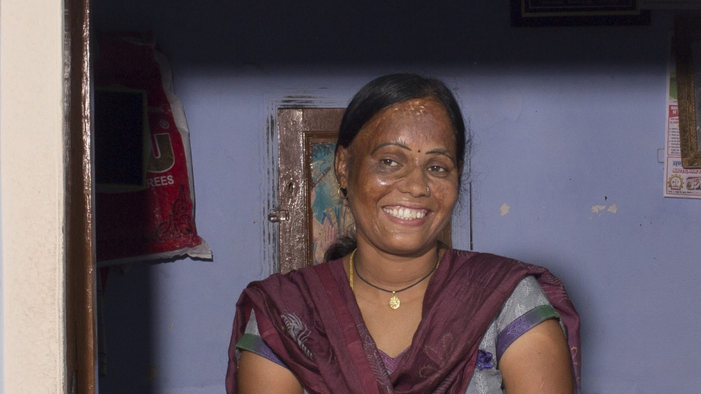 Anuradha Pareek, a 32-year-old lady from India, is standing in a draw way smiling.