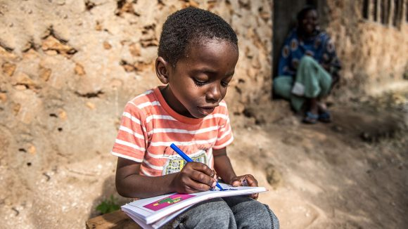 A young boy reads after having sight restoring surgery.