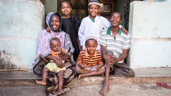 A family sit outside their home, smiling.