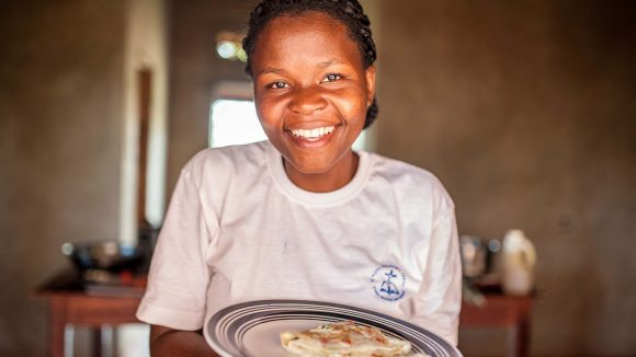 Women smiling at camera, holding plate with omelette