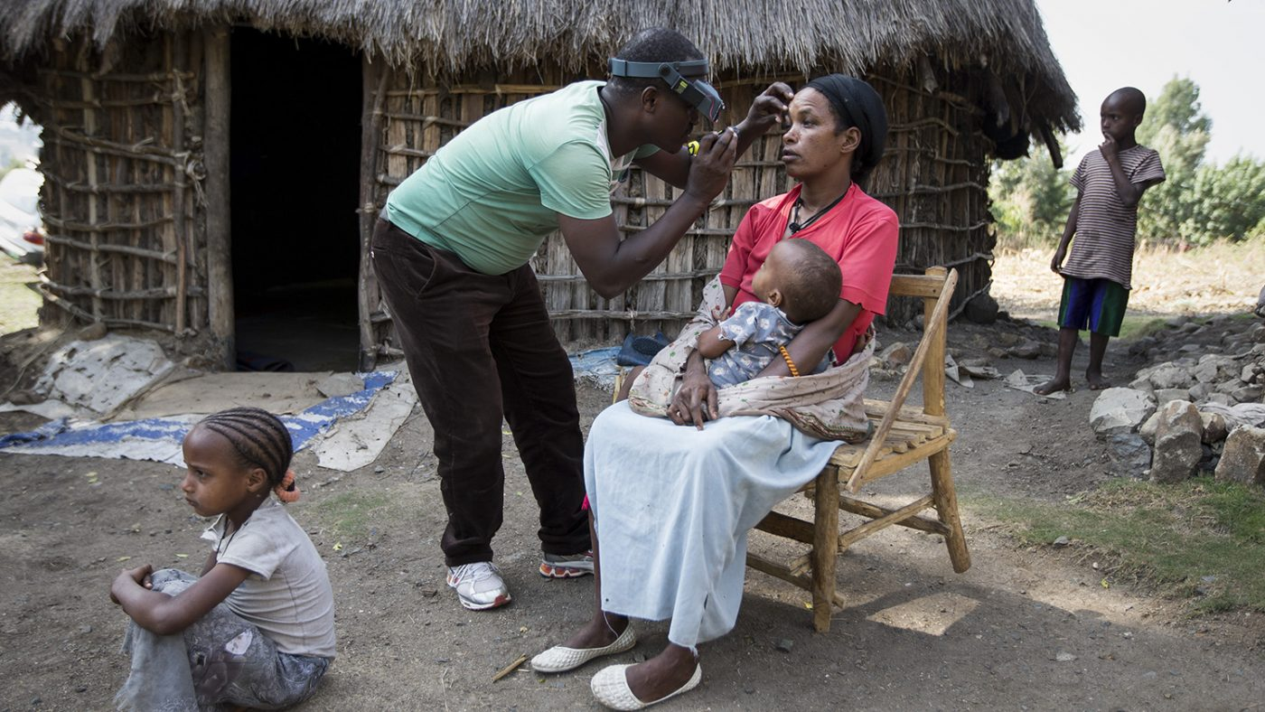 Hilbret is sitting on a wooden chair outside. A health worker is leaning over her head, examining her eyes. She has a child sitting on her lap.