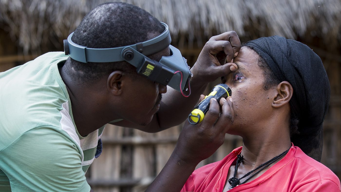 A health worker examines a woman's eyes.
